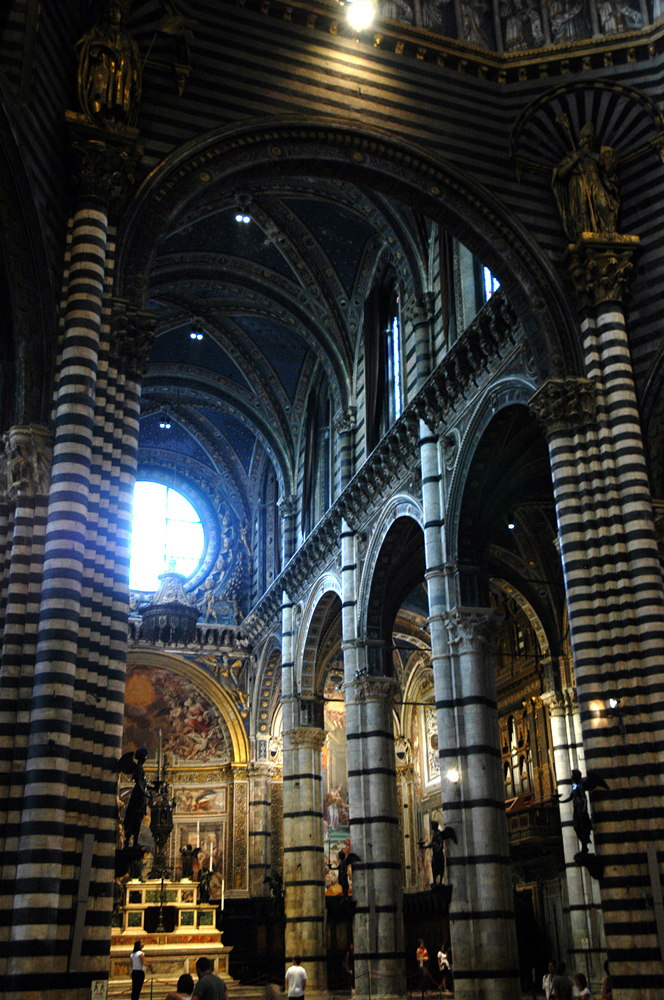 Black and white stone columns support the domed ceiling in Siena's Duomo.