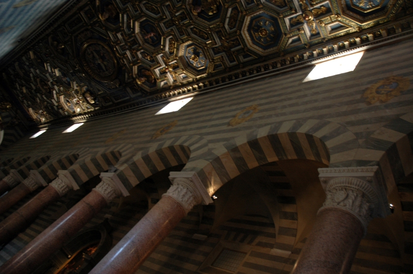A partial view of the ornate columns and coffered ceiling inside Volterra's cathedral.