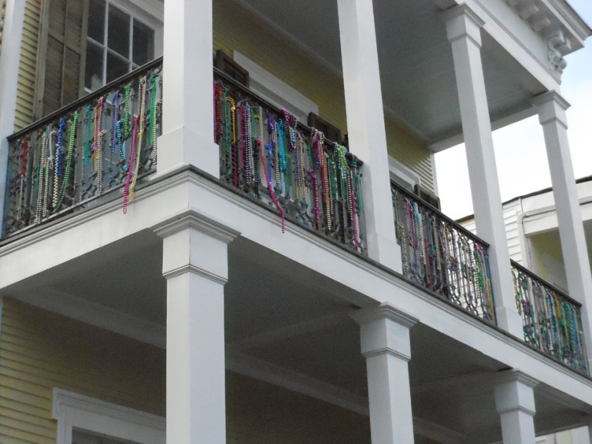 Beaded necklaces adorn the second-story iron railing on this home in the Garden District.